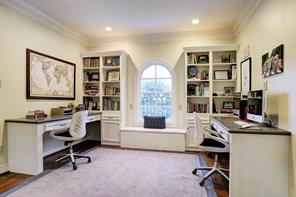 Built-in STUDY NOOK with an arched window with window seat below flanked by bookcases with storage cabinets below, and two built-in desks with pencil drawers and granite tops.  Fantastic office space for multiple children to do their homework!