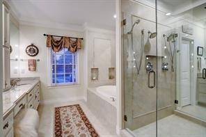 One of the MASTER BATHROOMS with a shared walk-in shower and deep soaking tub.  Also has wide vanity with marble top, travertine floors and customized walk-in closet.