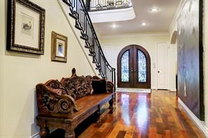 The decorative iron scroll work on the FRONT DOORS is echoed in the graceful stair railings and balusters.  Notice the wide-plank hardwood floors and the generously-sized FOYER.
