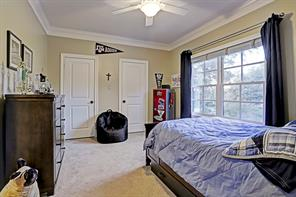 Another SECONDARY BEDROOM with large windows, plush carpeting and two closet entrances.