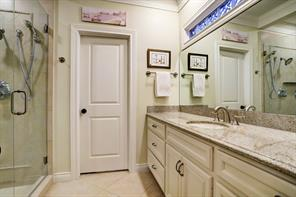 EN SUITE BATHROOM with large walk-in shower with seamless glass doors, a wide vanity with granite top and a customized walk-in closet.