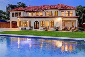 The BACK FACADE of this glorious home that showcases the covered back porch, bay windows upstairs and downstairs, and a wide expanse of grass and a motor court for playing.