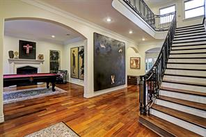 Another view of the STAIRCASE with wide hardwood stair treads.  Notice the graceful arches and the openness of this FOYER.