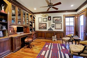 STUDY/LIBRARY has hardwood floors, large wood-framed windows and French doors leading to the covered back patio, wainscoting and an exceptional built-in desk & display cases flanked by bookcases.