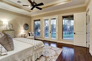Added warmth to the master suite with hardwood flooring and designer beige colored walls with cream trim. Wonderful windows and French glass doors leading to the covered patio with views of the lake.