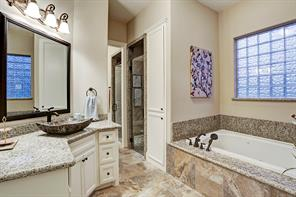 Dual sided master bath with separate sink/vanity areas, large whirl pool tub, walk-in shower and designer bowl sinks. Bathroom is highlighted with travertine tile and speckled granite.