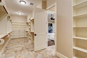 Massive walk-in master closet with lots of built-in storage and travertine flooring.