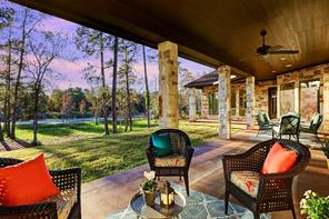 Beautiful backyard setting with dark ceilings, outdoor ceiling fans, limestone columns and stained concrete flooring.
