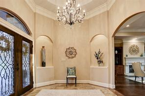 Exquisite foyer with tiered ceiling, double crown molding, art niches and double glass door with iron inlets show casing a beautiful crystal chandelier.