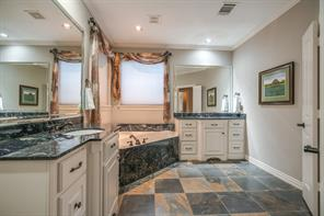 The master bath features more slate flooring, his and hers vanities and a spa tub!