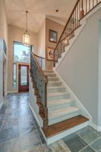 Ascend the custom wood and wrought iron staircase to the secondary bedrooms, game room, and more fantastic views!