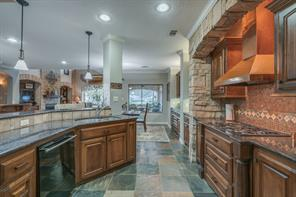 Beautiful granite countertops, a stacked stone feature AND a view of Lake Conroe all in the kitchen!