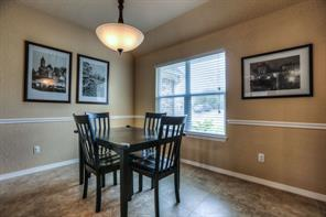 Formal dining area is at the front of the home, and also has tile flooring, and a chair rail.