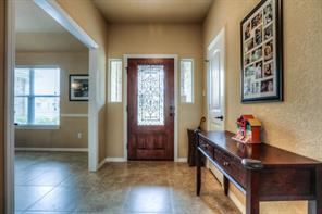 Entry way once inside shows nice tile flooring, and front door with decorative glass insert.