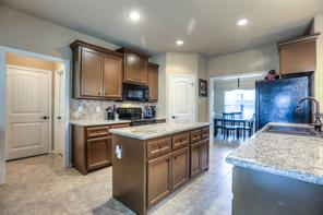 Beautiful kitchen has stained cabinets with hardware, granite counters, and tile flooring. Note decorative raised panel doors that are here and throughout the home.