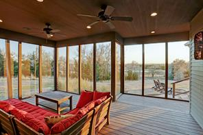 Screened in porch with view of fire pit and pond.