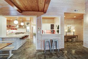 Front entry, kitchen and wet bar with ship lap walls and stained concrete floors.