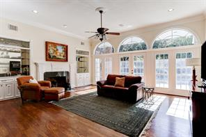 View of the fireplace surrounded by built-ins that are topped with custom glass transoms.