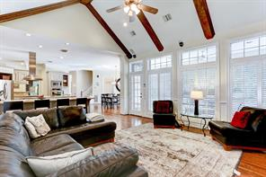 Architecturally pleasing family room with wood beams, back door and windows overlooking the gorgeous backyard.