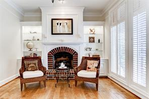 Cozy fireplace with brick surround flanked by custom lighted built in's, look like a page out of Veranda magazine.