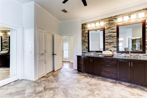 View of the updated custom vanity in the master bath with stone surround, dual sinks and extra storage areas.