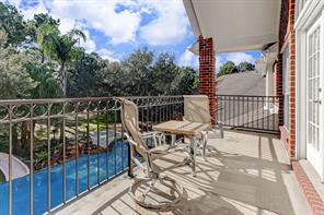 Outdoor balcony with French doors leading into the game room and overlooking the pool and lush grounds.