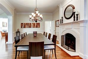View of the dining room with impressive fireplace adds the perfect ambience to your next dinner party.