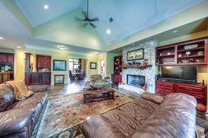 Very spacious living room with slate tile flooring, stone fireplace, and tons of built-in book shelves and cabinets.