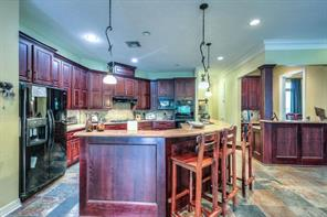Custom kitchen has beautiful stain grade cabinets, granite counters, double ovens and a large breakfast bar.