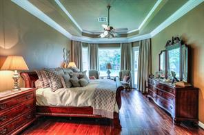 Master bedroom has wood flooring, raised ceiling, and nice picture windows that look to the backyard.