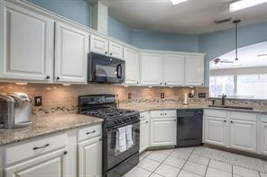 Great Kitchen Features Updated Granite Countertops, Tiled Backsplash, Under Cabinet Lighting and Oversized Sink.