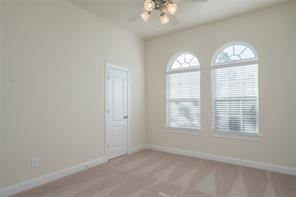 Second upstairs bedroom with carpeted flooring and high ceilings.