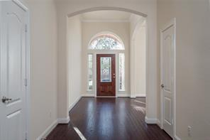 Lovely entry way with arched walk-through's and hardwood flooring.
