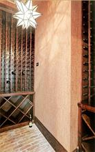 WINE ROOM - Climate controlled wine room with cork wallpaper.