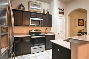Kitchen with hard surface counter tops great storage and breakfast bar.