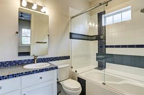 Attached to the upstairs secondary guest bedroom this full bathroom contains a shower, bath tub and beautiful blue tile work throughout.