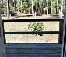 Step out the back door onto a new deck. Look at your land: the interior fence, and behind the trees another fence on the property line.