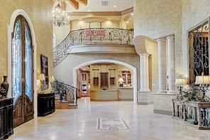 Upon arriving through the front doors (left) this view shows the grand foyer with soaring high ceilings and skillfully crafted Venetian plaster.