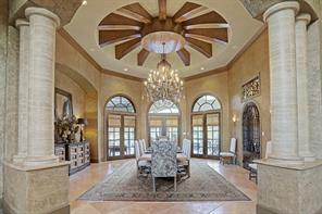 Elegant detailing in the formal dining room with its beautiful crystal chandelier, domed circular beamed ceiling, luxurious high ceilings, and lovely arched windows above the french doors. The middle set of french doors connect to the covered patio space providing open access to the beautiful views just outside.