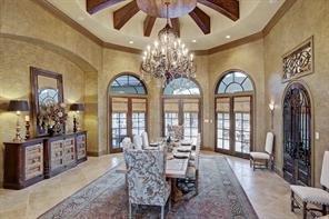 A defined nook to the left of the chandelier provides the perfect space for a buffet table. To the right, arched french doors lined with wrought iron detailing connects you to the 1,000+ bottle wine room.