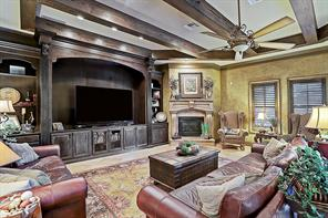 Spacious den with warm exposed wood beams and convenient built-in entertainment system with shelves and drawers. Warm and inviting, this den is cozy and great for everyday lounging.