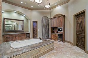 Three gorgeous chandeliers line the high ceilings creating the ultimate focal point in this grand bath. Along with the built-in Bosch espresso/coffee maker and wine refrigerator, this master suite bath is adjoined to a luggage closet (left) and the magnificent master closet.