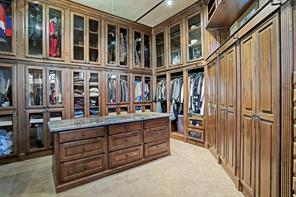 What a remarkable master closet! This side of the closet has glass front doors and plenty of built in drawers in the massive granite island. The railing is meant for the built in library ladder (seen in the next photo) so items in the top drawers and shelves may be reached.