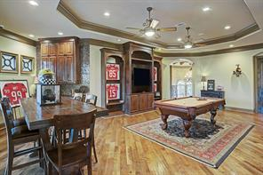 At the top of the stairs lies the extra large game room with gorgeous tray ceiling and built in television nook. To the side, a convenient wet bar with wine refrigerator provides an area to serve refreshments for guests.