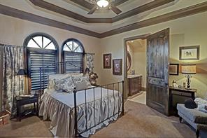 Charming secondary bedroom located on the first floor with gorgeous tray ceiling and large en suite bath.