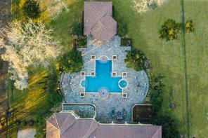 Eagle eye's view of the backyard displaying the grand pool and landscaping which mirrors spectacular symmetry. The expansive backyard has hosted celebrated galas and fundraisers, entertaining with ease. The property includes the lot to the right of the far right fence for a total of 3.58 acres.