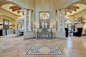 Upon entering the majestic front doors, a stunning tile mosaic can be seen in the front foyer. Straight ahead, the wine room is flanked by the formal dining room on the left and the formal living room on the right. Magnificent stone columns frame the sides of each room. These are just a few of the intricate and thought out details that you can see throughout the home.