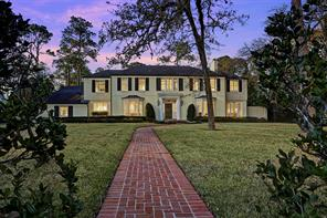 View from the curb with wide grassy lawn across the front dotted with mature trees, landscaped planting beds and curving brick walkway from curb to porch. Professionally landscaped yard with mature trees; ornamental trees; massed azalea plantings; flowering shrubs; established planting beds with seasonal flowers; Rainbird® automatic sprinkler system and exterior building accent and landscape lighting; side driveway on left side of home and wrought iron pedestrian gates on each side of home.