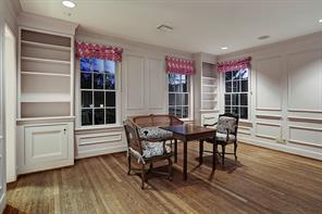 """GAME ROOM AND PLAY ROOM – 17' 9"""" X 20' 4"""": Adjacent to Kitchen;  Floor-to-ceiling 2-tiered built-in storage cabinets; Louvered door conceals Rheem® 50 gallon gas hot water heater; Ceiling-mounted rail lighting with adjustable and repositionable lamps; Ceiling fan with light; Wall of tall divided-light windows on either side of divided-light French door that opens to rear Enclosed Motor Court/Play Area; Wide-plank hardwood flooring with 9"""" tall extended-height baseboards"""