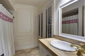 """BEDROOM # 2 WITH PRIVATE BATH – 17' 2"""" X 12' 2"""": Formal block-paneled walls;Two built-in display cases with adjustable shelves, cornice tops and cabinets; Tall divided-light windows; Recessed lighting; Recessed ceiling speakers; Hardwood floor; Two  Closets, Each – 3' 5"""" x 21"""";  Private Bath: Paneled accent wall, white basin set into slab marble counter and framed vanity mirror; Recessed privacy alcove for Kohler® toilet; Kohler® programmable whirlpool tub and shower; Marble"""